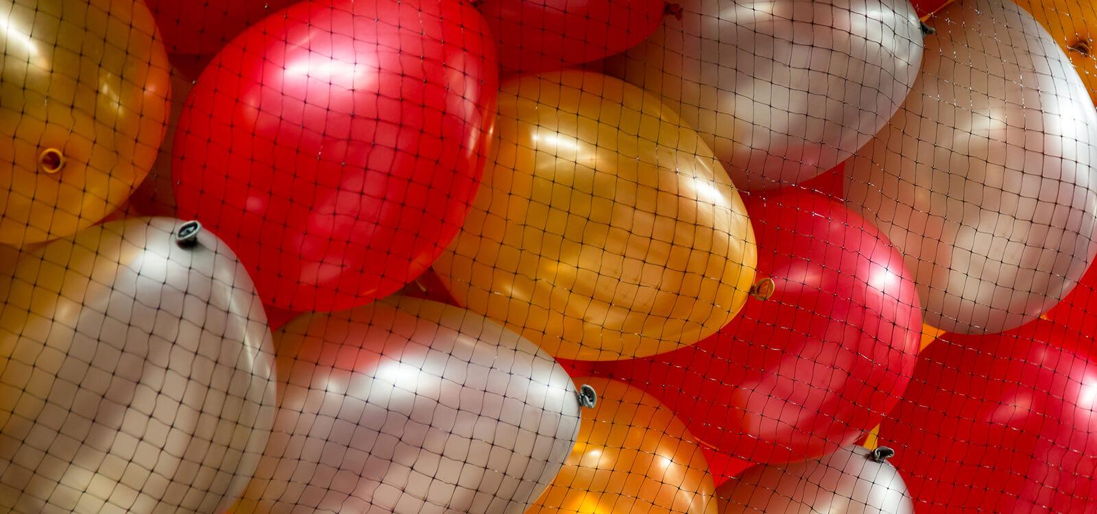 Ballon rouge, or et blanc dans un filet