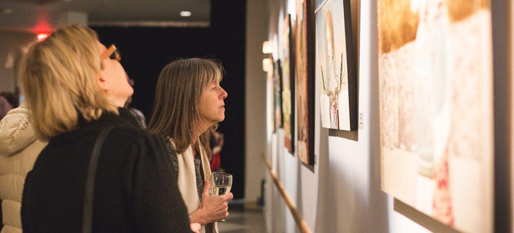 Dame qui regarde une toile lors d'une exposition