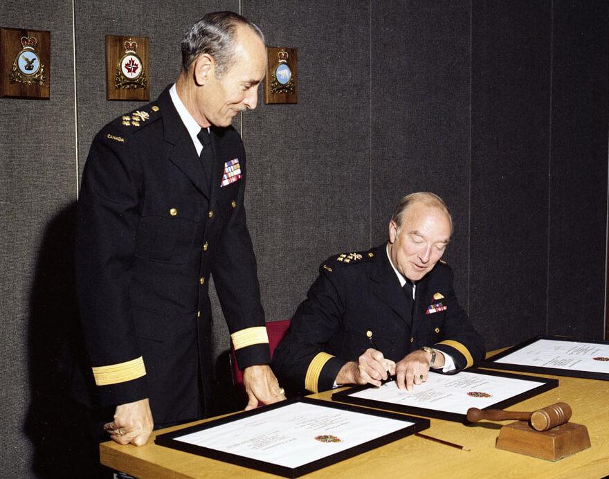 Signature des parchemins lors de la passation de commandement du Chef d'état-major de la Défense entre le général Dextraze et l'amiral Falls, 31 août 1977