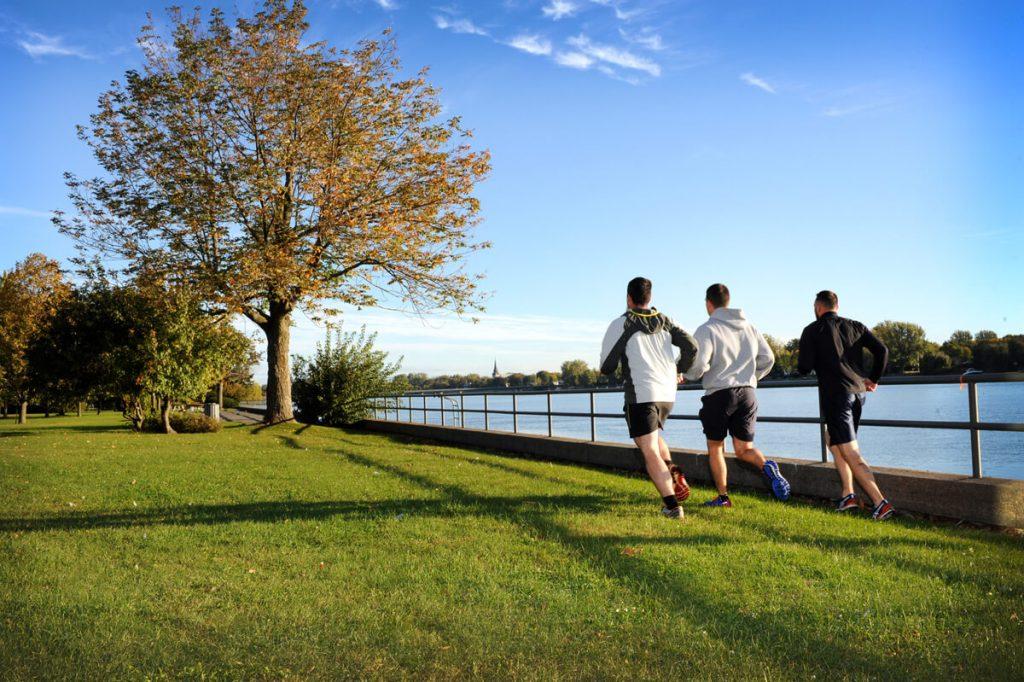3 hommes qui courent sur le bord de l'eau à la Corporation du Fort St-Jean