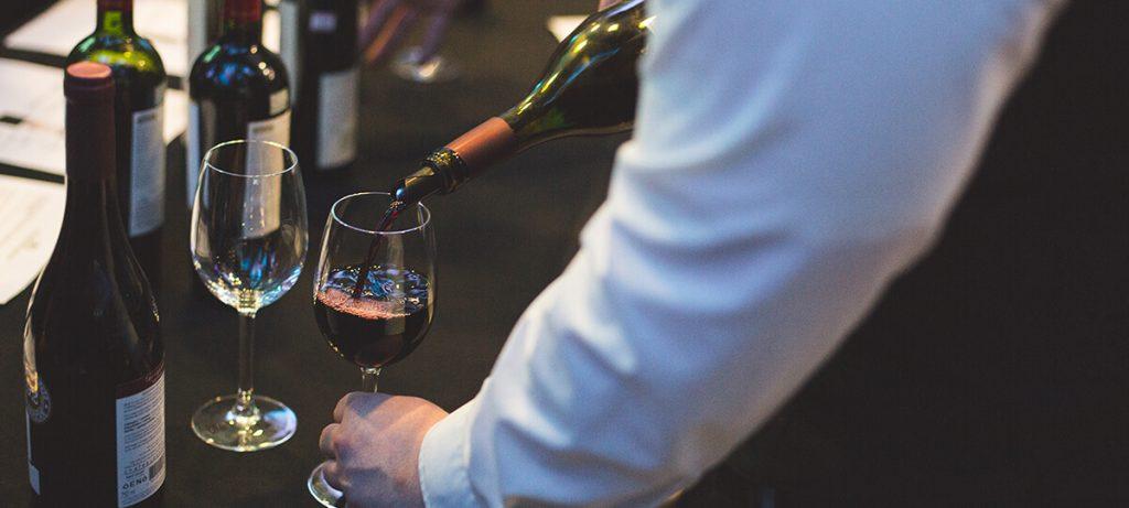 Serveur qui serre un verre de vin rouge