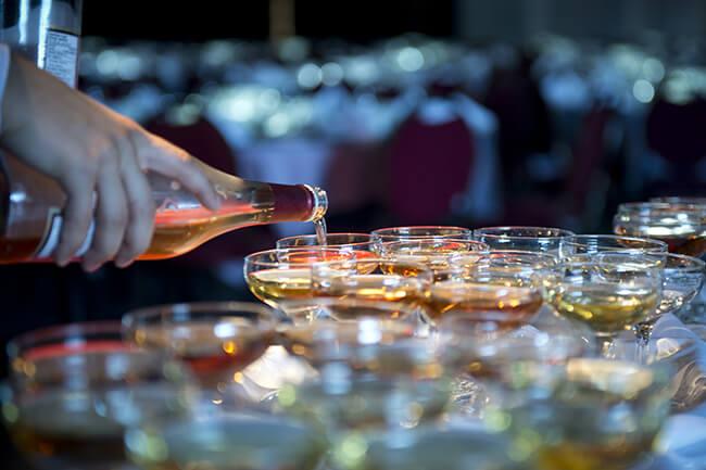 Serveur qui remplit plusieurs verres de champagne